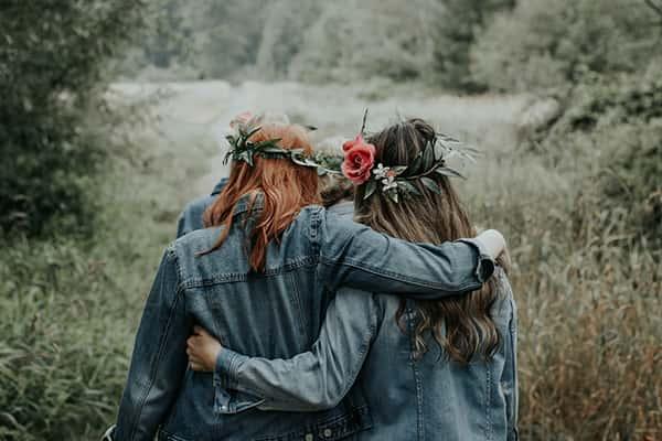Deux amies de dos avec des fleurs dans les cheveux se tiennent bras dessus bras dessous
