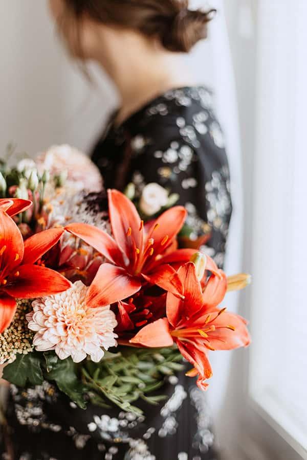 Femme de profil tenant un bouquet de fleurs rouges